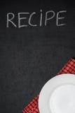De receptentitel wordt geschreven in krijt op een bord en een lege plaat Stock Foto