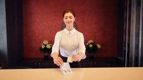 De receptionnist bij het bureau van de hotelontvangst ontmoet gasten 4K stock video
