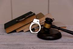 De rechtershamer en handcuffs liggen naast stapel van boeken op concrete achtergrond stock foto's