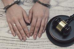 De rechtershamer op houten achtergrond met vrouw dient handcuffs in royalty-vrije stock afbeelding