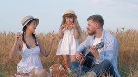 De recreatie van het familieplatteland, jonge papa speelt gitaar wanneer zijn mooie vrouw in strohoed en witte kleding danst stock footage