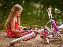 De recreatie van het fietsmeisje en PC van de horlogetablet zitten dichtbij water Royalty-vrije Stock Foto's
