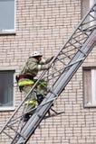 De redder neemt op de brandtrap toe tot een gebouw met meerdere verdiepingen stock foto