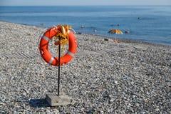 De reddingsboei hangt op het strand voor de veiligheid van mensen bij het zwemmen op overzees Stock Fotografie