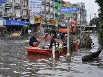 De reddingsmensen wachten in hun boot in een overstroomde straat van Pathum Thani, Thailand, in Oktober 2011 stock fotografie