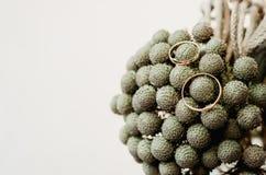 De reeks huwelijks gouden ringen op grijze, ronde boeketbrunia bloeit in vaas rustieke stijl, witte achtergrond Stock Foto's