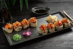 De reeks sushi rolt op een zwarte rechthoekige plaat op een zwarte houten achtergrond stock foto