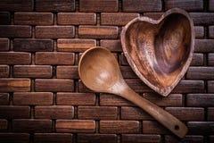 De reeks van heartshaped houten kom en lepel op houten backcloth Stock Fotografie