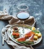 De reeks van het wijnvoorgerecht Het glas rode wijn, uitstekend vaatwerk, brushetta met kers, droge tomaten, arugula, parmezaanse Stock Fotografie