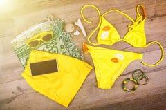 De reeks van strand kleedt gele bikini, armbanden, borrels, glazen op donkere houten achtergrond Hoogste mening Ligstoel op stran Stock Foto's