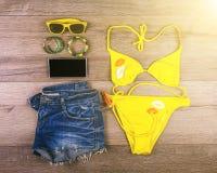 De reeks van strand kleedt gele bikini, armbanden, jeansborrels, glazen op donkere houten achtergrond Hoogste mening Ligstoel op  Stock Afbeelding