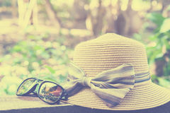 De reeks van vakantietoebehoren zoals zonnebril en hoed op bokehachtergrond, de zomerconcept, sluit omhoog zonnebril en hoed Stock Fotografie