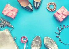 De reeks van de vlakte van maniertoebehoren legt van de halsbandjuwelen van de schoenenhandtas de zilveren kleur op de blauwe rui stock foto