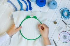 De reeks voor borduurwerk, borduurwerkhoepel, linnenstof, draad, schaar, borduurde naaldbed stock afbeeldingen
