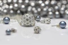 De reeksen van close-upjuwelen beslagen zilveren en zwarte parelsoorringen en tegenhangers op acrylraad Stock Fotografie