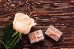 De regalos color de rosa y un par de envueltos frescos en el fondo de madera Fotografía de archivo libre de regalías