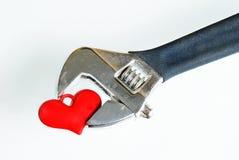 De regelbare Moersleutel knijpt het rode hart. Stock Foto's