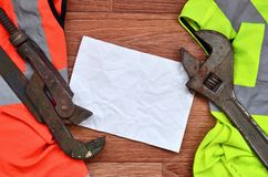 De regelbare moersleutels en het document liggen van overhemden van een de oranje en groene signaalarbeider Stilleven verbonden a royalty-vrije stock foto