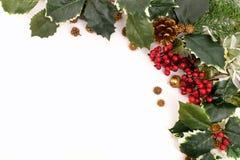 De regeling van de Kerstmisdecoratie met hulst, bessen en denneappels Royalty-vrije Stock Foto's