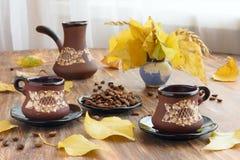 De regeling van de ontbijtlijst met koppen van koffie, gele bladeren Stock Foto