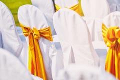De regeling van huwelijksstoelen voor huwelijkstrefpunt verfraait met witte stoffendekking met gouden organza royalty-vrije stock afbeelding