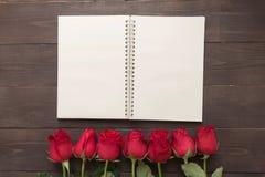 De regeling van rode rozenbloem met notitieboekje is op nastreeft Stock Foto