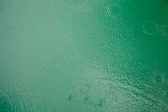 De regen laat vallen cirkels op groene meerwaterspiegel royalty-vrije stock fotografie