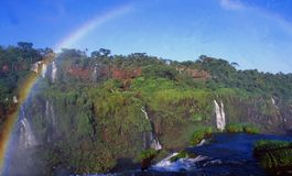 De regenboog over het Iguacu-water valt bij de pensionair van Brazilië, Argentinië en Paraguay stock afbeelding
