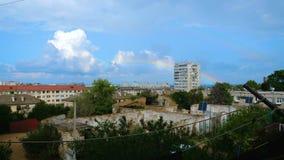 De regenboog verdwijnt over het flatgebouw stock footage