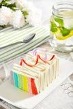 De regenboogcake met gegoten water en nam op de achtergrond toe Royalty-vrije Stock Afbeelding