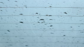De regendalingen vlakken op Vensters af stock footage