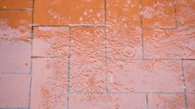 De regendruppels die op terras vallen en het gebeurt een grote plons van water en bellen stock video