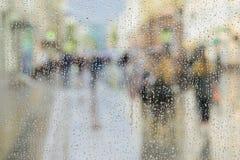 De regendruppels op vensterglas, mensen lopen op weg in regenachtige dag, vage motie abstracte achtergrond Concept het winkelen royalty-vrije stock foto