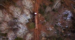De registrerenvrachtwagen die met vers gezaagd hout wordt geladen verlaat de registrerenplaats in taiga