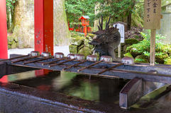 De reinigingsfontein van Chozuya van het Hakoneheiligdom met draakbeeldje stock foto