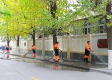De reinigingsmachines vegen straat Stock Afbeeldingen