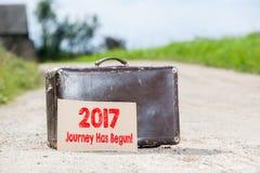 2017 is de Reis begonnen Oude reizende koffer bij de landweg Stock Fotografie