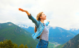 De reis de gelukkige vrouw verse lucht van bergen geniet heft omhoog handen op Stock Foto