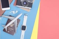 De reis heeft toebehoren op blauwe gele roze achtergrond met paspoortcamera en vliegtuig bezwaar royalty-vrije stock afbeeldingen