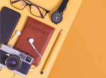 De reis heeft toebehoren op oranje achtergrond met paspoortcamera en vliegtuig bezwaar stock afbeelding