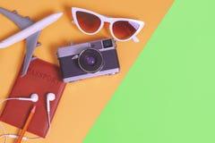 De reis heeft toebehoren op oranje groene achtergrond met paspoortcamera en vliegtuig bezwaar royalty-vrije stock foto's