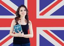 De reis in het Verenigd Koninkrijk en leert engelstalig Mooie studentenholding phrasebook tegen de Britse vlagachtergrond stock foto's