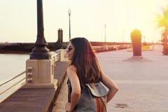 De reis hipster vrouw met zonnebril en de rugzak genieten van zonsondergang Achtermening van reismeisje in openlucht met de gloed royalty-vrije stock foto