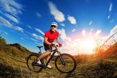 De reis van de fietsertoerist op bergfiets Autumn Landscape Sportman op fiets in rood Jersey en witte helm Royalty-vrije Stock Foto