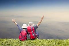 De reis van de paarrugzak het ontspannen bovenop een berg stock foto