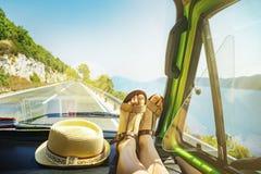 De reis van de de zomerweg met jonge vrouwelijke benen op dashboard binnen van klassieke oldtimerbestelwagen die naast overzeese  stock foto