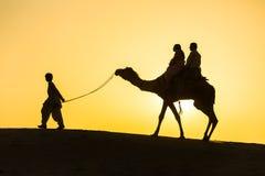 De reisachtergrond van Rajasthan - kameelsilhouet in duinen van de woestijn van Thar op zonsondergang stock foto's