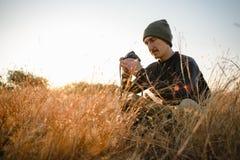 De reisfotograaf bekijkt het scherm van zijn camera Stock Foto