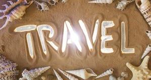 De Reissymbool van de handtekening in het zand De Zeeschelp van de kammossel op Roze Bovenkant v Royalty-vrije Stock Foto