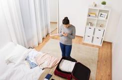 De reiszak van de vrouwenverpakking thuis of hotelruimte Stock Afbeelding